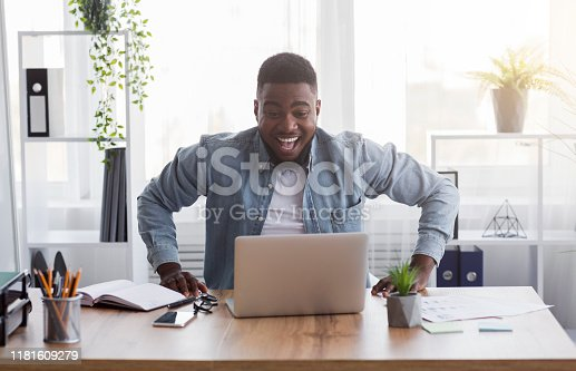 istock Joyful black employee looking at laptop screen with excitement 1181609279
