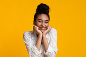 istock Joyful Black Girl Holding Hands On Cheeks And Smiling At Camera 1210728931