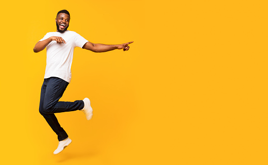 Joyful black millennial guy jumping up and pointing aside, panorama with free space, yellow studio background. Happy african american man jumping in the air, showing advertisement or text