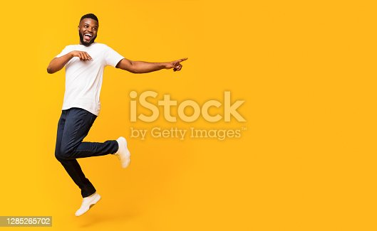 istock Joyful black guy jumping up and pointing aside 1285265702