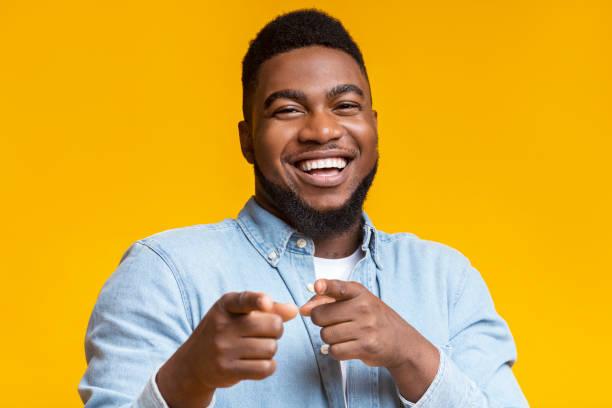 Joyful black guy pointing fingers at camera on yellow background stock photo