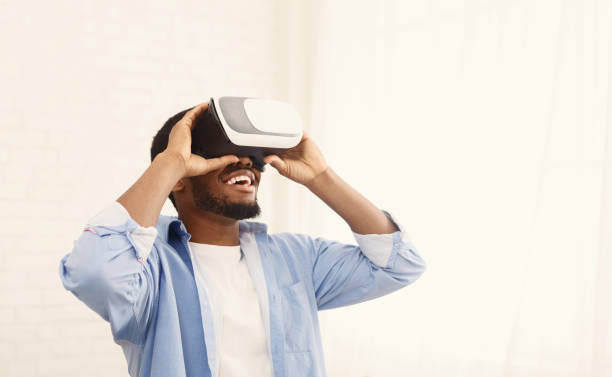 Joyful black man using VR headset at home stock photo