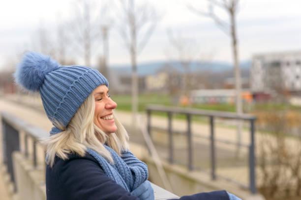 Joyful blond woman in a warm winter outfit stock photo