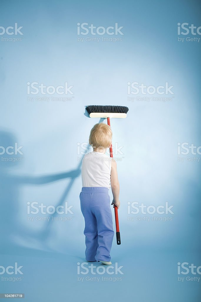Joyful boy cleaning wall with swab royalty-free stock photo