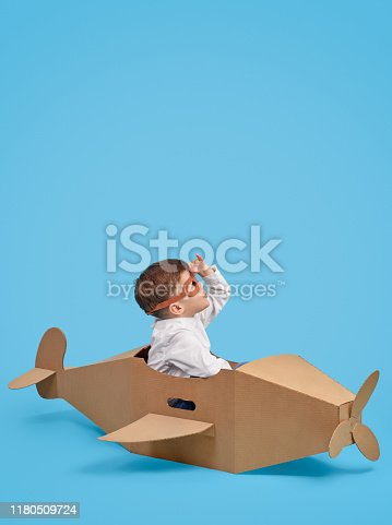 Side view of attentive kid in pilot helmet sitting at handmade cardboard airplane and looking up over blue background