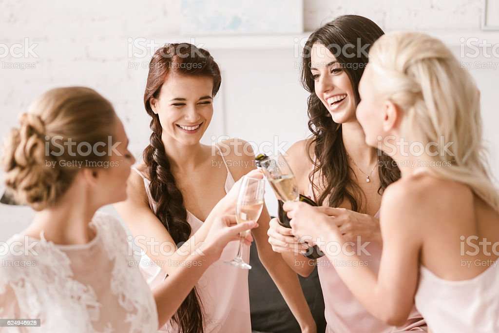 Joyful bride and bridesmaids having party at home - foto stock