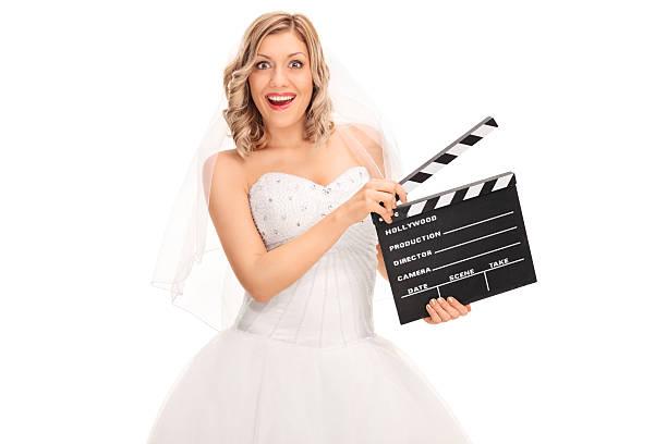 fröhliche braut hält ein film erste klappe fällt - wedding photography and videography stock-fotos und bilder