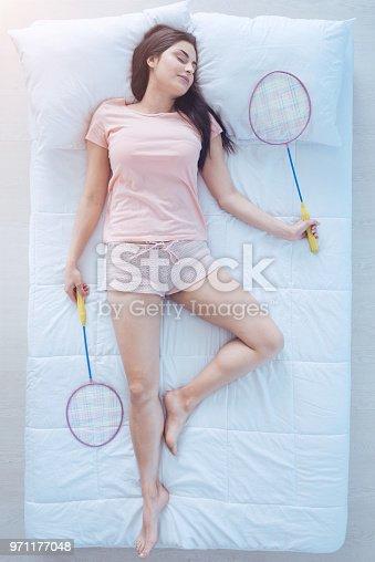 971177184 istock photo Joyful brunette sleeping with badminton rackets 971177048