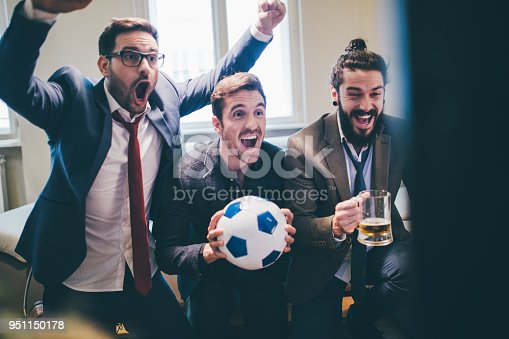 istock Joyful business men supporting their favorite football teams in excitement 951150178