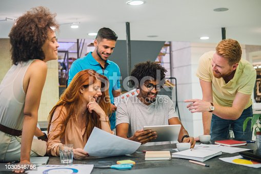 Happy young people working together at office