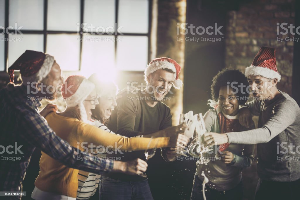 Joyful business team having fun while opening champagne during Christmas celebration in the office. stock photo