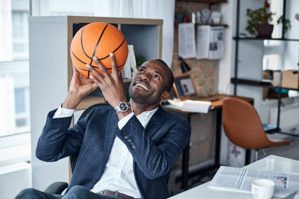 Joyful businessman is keeping ball in hands Playful mood. Cheerful young african manager in suit is sitting in office and holding orange basketball with smile. He is looking up while being ready to throwing it basketball sport stock pictures, royalty-free photos & images