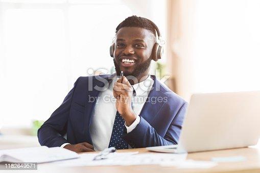 1003539592 istock photo Joyful businessman singing and listening to music with headphones 1182649571