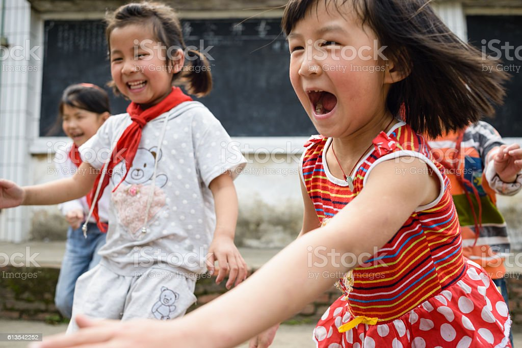 Joyful Chinese Elementary School Kids Playing Outdoors stock photo