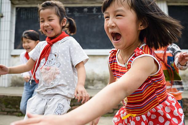 Joyful Chinese Elementary School Kids Playing Outdoors - Photo