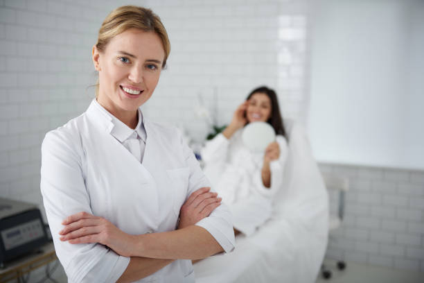 Joyful cosmetologist standing in her cabinet wile client resting on daybed stock photo