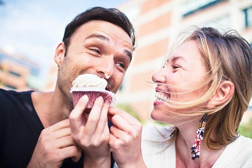 Joyful couple eating cupcake outdoors