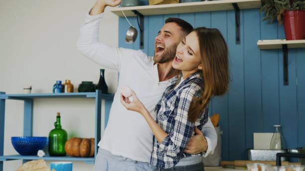 うれしそうなカップルでは、午前中に自宅の台所で楽しい踊りと歌があります。 - ボーイフレンド ストックフォトと画像