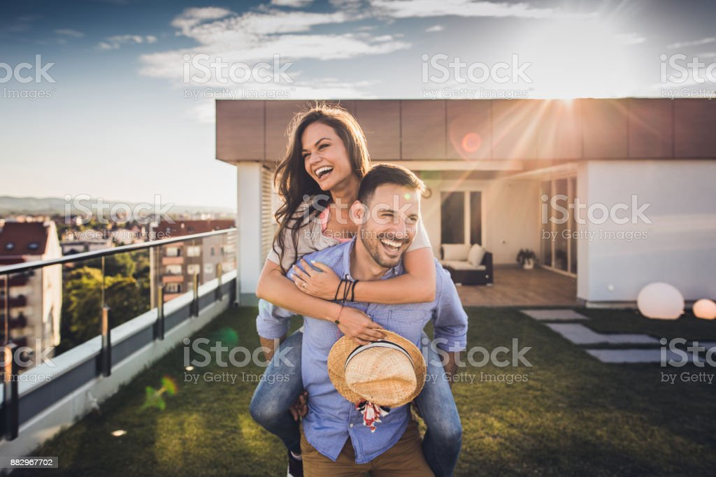 Joyful couple having fun while piggybacking on a penthouse terrace. stock photo