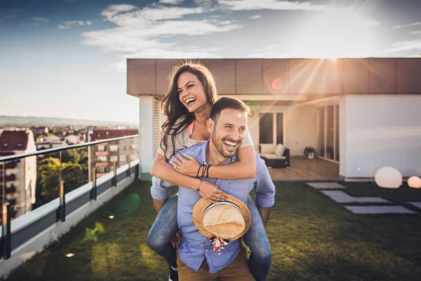 freudige paar spaß beim huckepack auf einer penthouse-terrasse. - dachgarten stock-fotos und bilder