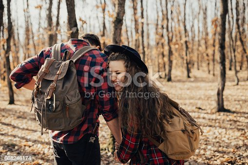 istock Joyful couple laughing in the middle of the forest during Autumn 668246174