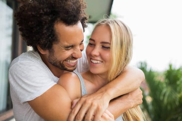 Joyful couple laughing together outdoors stock photo