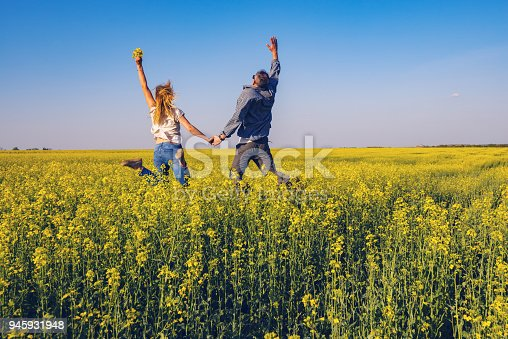 Joyful couple with open arms is jumping on the field of yellow flowers under the blue sky - a happiness and freedom in nature. Back view.