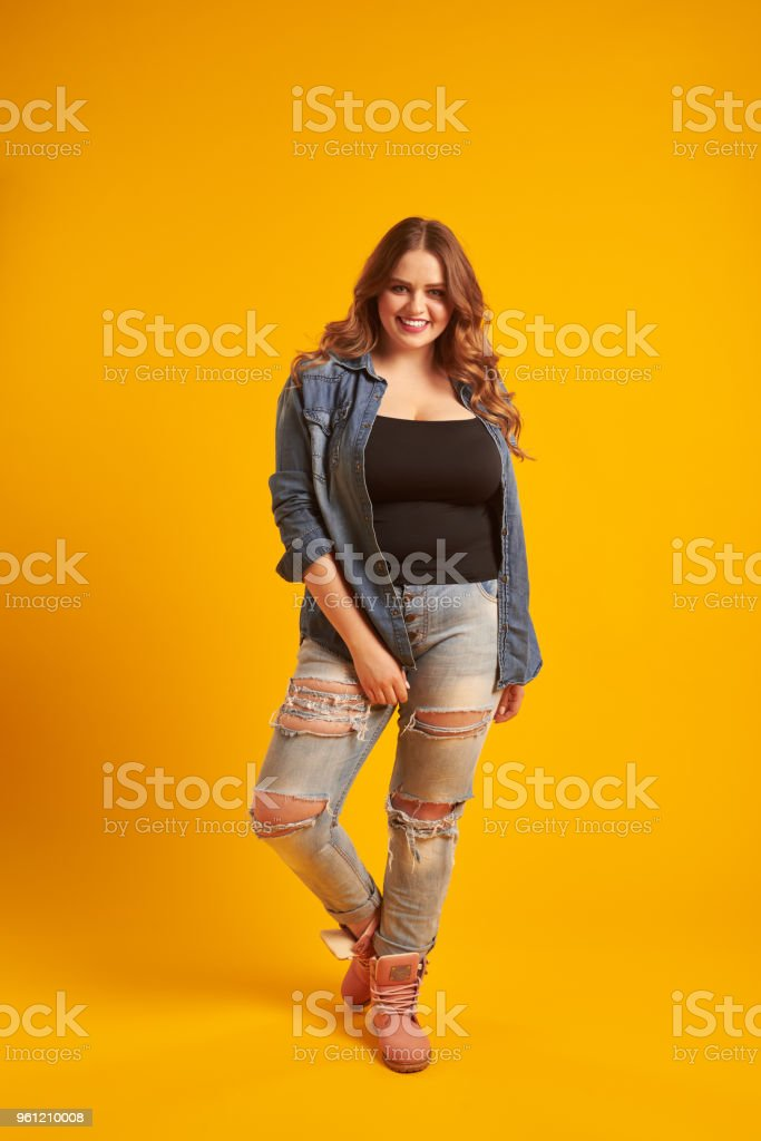 Joyful curvy girl in casual outfit posing at studio stock photo