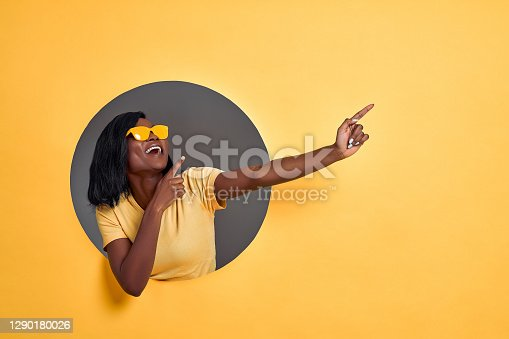 istock Joyful dark skinned woman points fingers aside , pleased by big sale prices, wears sunglasses and casual orange t shirt, models over yellow background, shows copy space for your advert. 1290180026
