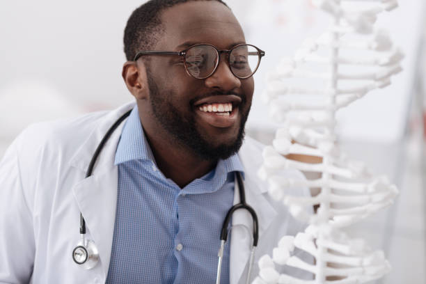Joyful delighted scientist smiling Successful research. Joyful smart genius scientist looking at the DNA model and smiling while completing his research dna purification stock pictures, royalty-free photos & images