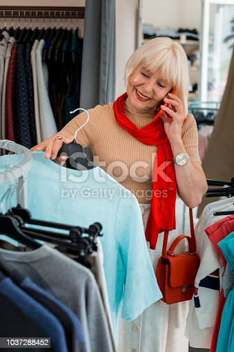 istock Joyful elderly woman choosing summer dress while talking via mobile phone 1037288452