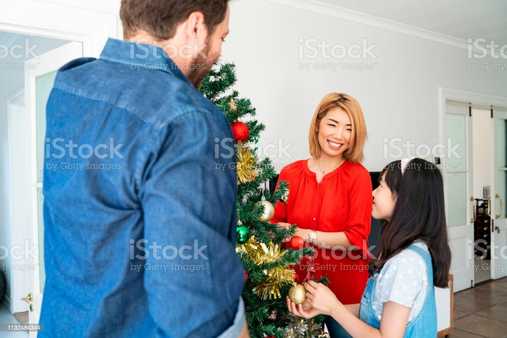 Happy family decorating Christmas tree at home. Mother and father are...