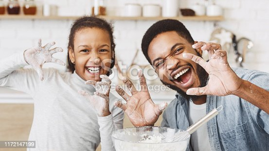 Happy african dad and daughter having fun while cooking pastry, making funny growling faces and imitating animal paws, kitchen interior