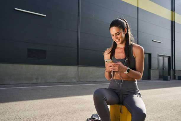 Joyful female fitness guru updating her social media stock photo