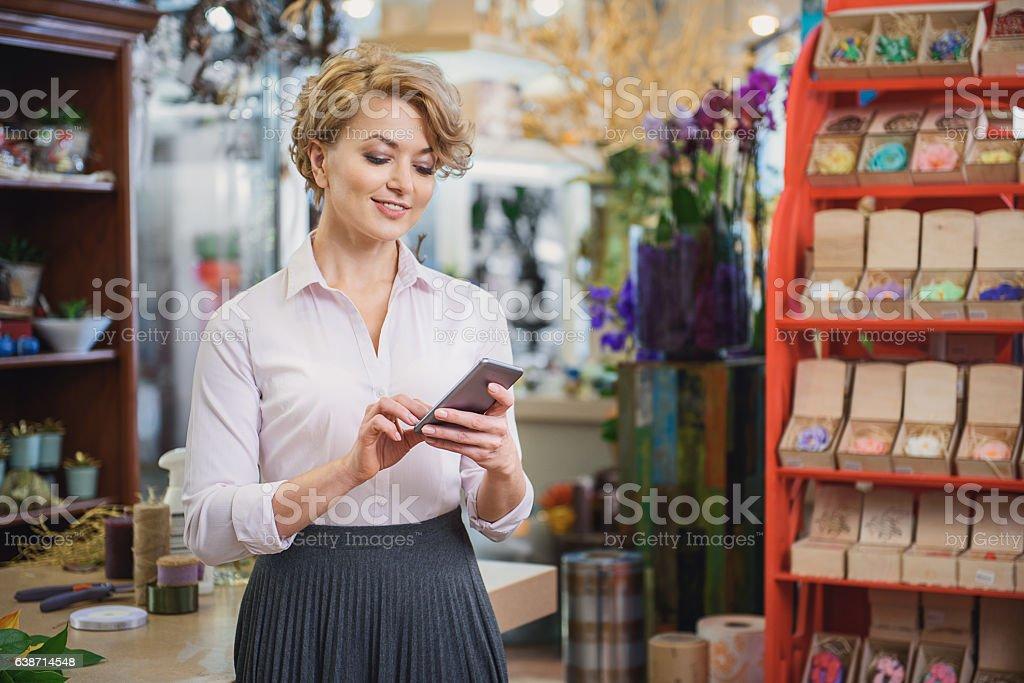 Joyful female florist using mobile phone bildbanksfoto