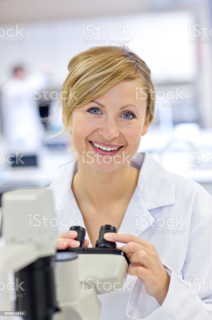 Joyful female scientist using a microscope stock photo