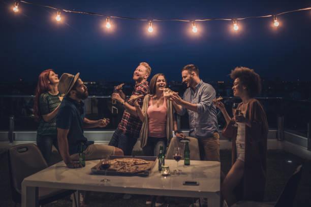 fröhliche freunde mit einem abendessen feiern in der nacht auf der terrasse. - terrassen lichterketten stock-fotos und bilder
