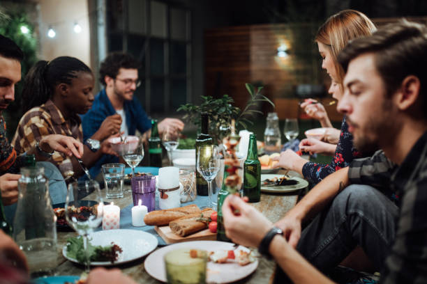 Joyful friends having a dinner party during the night stock photo
