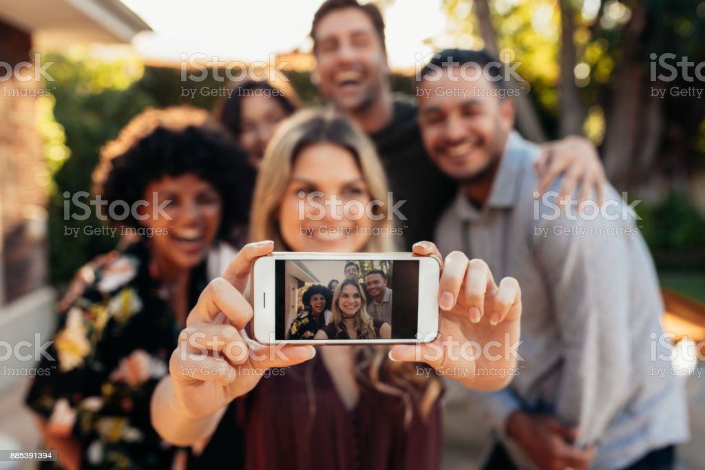 Joyful friends taking selfie during outdoor party stock photo