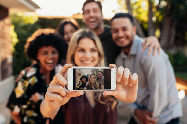 joyful friends taking selfie during outdoor party - reunion stock photos and pictures