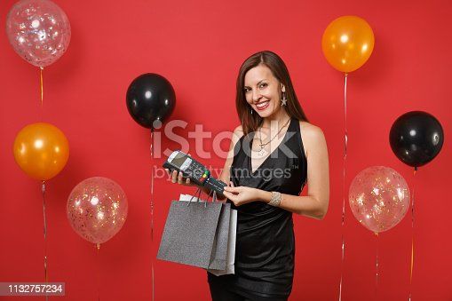 istock Joyful girl holding wireless modern bank payment terminal credit card packages bags with purchases after shopping on red background air balloons. Happy New Year, birthday mockup holiday party concept. 1132757234
