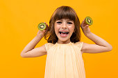 joyful girl holds kiwi on a yellow background.