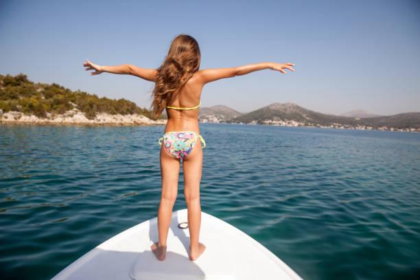joyeuse fille été debout sur la proue de vacances et profiter de la vue - fille dos photos et images de collection