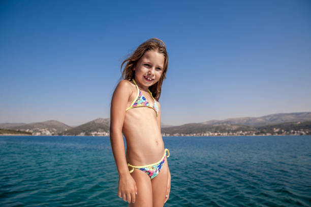 joyful girl on summer holiday standing on  bow and enjoy the view - girl alone in swimsuit stock photos and pictures