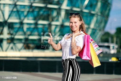 istock Joyful girl shows thums up with bright shopping packages at the mall. The final big summer and autumn sale 1148501456