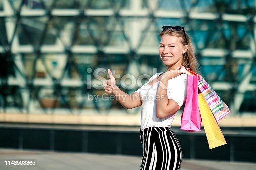 istock Joyful girl shows thums up with bright shopping packages at the mall. The final big summer and autumn sale 1148503365
