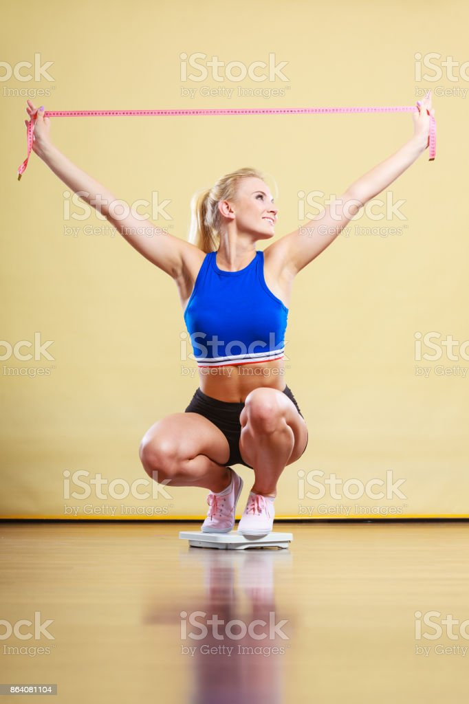 Joyful girl standing on bathroom scales royalty-free stock photo