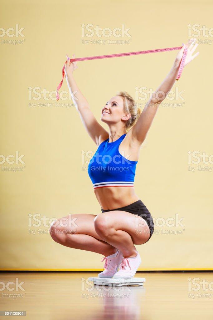 Joyful girl standing on bathroom scales royalty-free stock photo