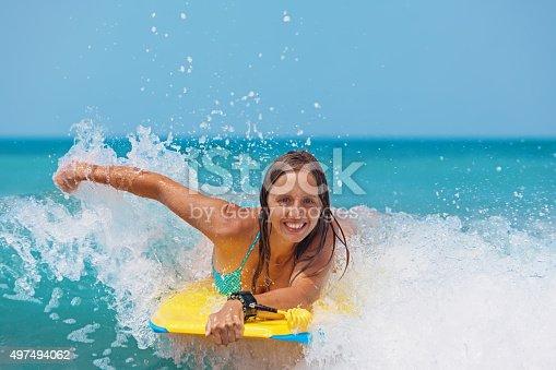 583830686istockphoto Joyful girl swimming with boogie board on the sea waves 497494062