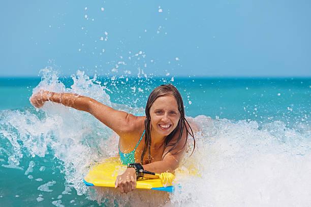 Joyful girl swimming with boogie board on the sea waves stock photo